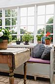Holztisch und alte Bank am Sprossenfenster mit Geranien auf der Fensterbank