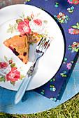 Ein Stück Beerenkuchen auf Teller mit Rosendekor