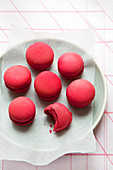 Red macarons on a plate, one bitten
