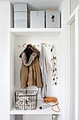 Weiße Garederobe mit Winterjacke, darüber Ablage mit Boxen in Wandnische