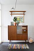 Retro Sideboard mit Zimmerpflanzen, darüber Lampenschirm auf Ablage