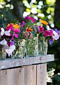 Sommerblumen in Wassergläsern auf einer Bretterwand