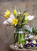 Osterstrauß mit Tulpen, Narzissen und Haselzweigen im Schraubglas