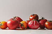 Variety of ripe fresh organic gardening tomatoes on white marble table