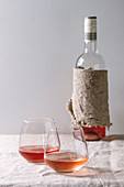 Two glasses of different rose wine standing on grey linen table cloth with bottle