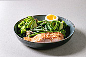 Ketogenic low carb diet dinner grilled salmon, avocado, broccoli, green bean and soft boiled egg