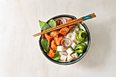 Poke bowl with soy sauce marinated salmon, rice, avocado and tofu cheese served in ceramic bowl with chopsticks