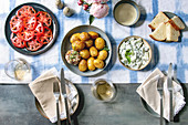 Young baked potatoes, tomato carpaccio, cucumber salad, bread, wine, sauce and flowers