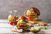 Vegan burgers with carrot and avocado in classic bun, served on wooden board with avocado sauce and ingredients