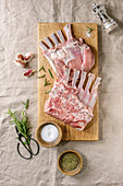 Raw uncooked rack of lamb on wooden cutting board with salt, herbs rosemary, pepper and garlic