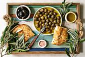 Verschiedene eingelegte Oliven serviert mit Ciabatta auf Tablett