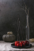 Red caramel apples sweet autumn dessert served with branches and decorative pumpkins in black ceramic plate
