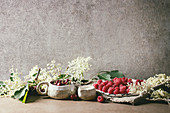Fresh cherry and raspberry berries in ceramic mug and plate, elderflowers, jug of cream on kitchen table