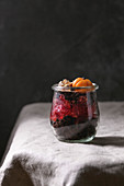 Layered Halloween dessert chocolate biscuit, raspberry jelly, nuts, marzipan pumpkin in glass jar