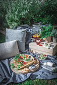 Picknick im sommerlichen Garten mit Bruschetta, Käse und Getränkespender