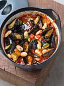Mussel and bean stew with tomatoes and zucchini