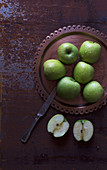 Metal knife placed near plate with fresh green apples on shabby tabletop