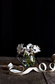 Coiling ribbon placed on timber tabletop near glass vase with white flowers on black background