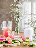 Cold glass jug of iced pink lemonade with watermelon and lime slices on rustic kitchen table and bunch of gypsophila flowers