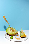 From above cut ripe appetizing sweet pitted melon on plate with spoon and fork in blue table background