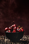 From above tasty appetizing ripe cherry in black brown shining under sunlight on rustic wooden background