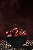 Rote sonnenbeschienene Kirschen mit Wassertropfen in einer Schale