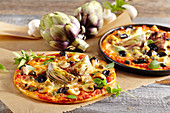 Small pizzas with artichokes, olives and mushrooms