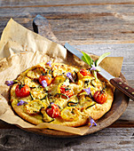 A small pizza with zucchini, cherry tomatoes and sage