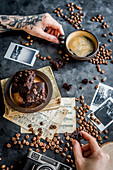 A coffee break with brownies and cup of coffee in between old photos and coffee beans
