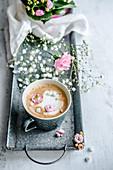 Eine Tasse Kaffee dekoriert mit Milchschaumherz und Blüten
