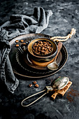 Kaffeebohnen im Schälchen, im Vordergrund Sieb mit Kakaopulver