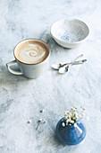 Kaffee mit Milch in Keramiktasse auf hellem Untergrund