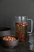 Glass carafe of mulled wine with apples and cinnamon