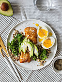 Fried fish with quinoa, kale, avocado and a soft-boiled egg