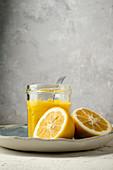 Lemon Curd im Schraubglas, daneben Zitronenhälften