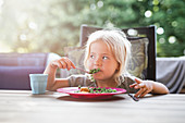 A little girl eating fish and peas on a terrace