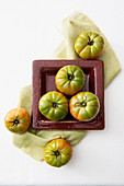 Green tomatoes in a square ceramic bowl