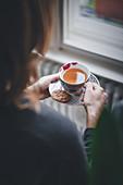 Frau mit heißem Tee und Gewürzplätzchen