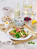 Edamame-Sandwich, Chia-Pudding und Frühstücksei auf Holztablett
