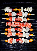 Raw fish skewers with cherry tomatoes on a barbecue