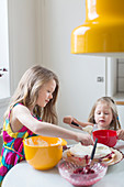 Two girls making a cake