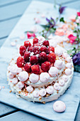 A two-tier meringue cake with raspberries