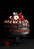 A multi-layer chocolate cake decorated with berries and flowers