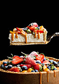 A cheesecake with caramel sauce and fresh fruit with a piece on a cake slice