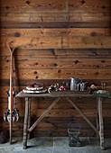 An rustikaler Holzwand angelehnte Skier neben Buffet mit Salami, Wein und Brot