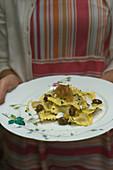 Frau serviert Artischockenravioli mit karamellisierten Zwiebeln und Oliven