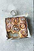 Cinnamon and orange buns in a square baking tin