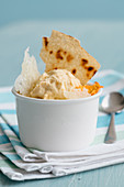 Creamy zucchini flower ice cream with a crispy bread chip and pecorino