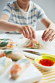 Kind beim Zubereiten von Reispapierröllchen mit Garnelenfüllung