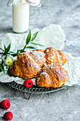 Croissants for breakfast sprinkled with powdered sugar served with raspberries and milk
